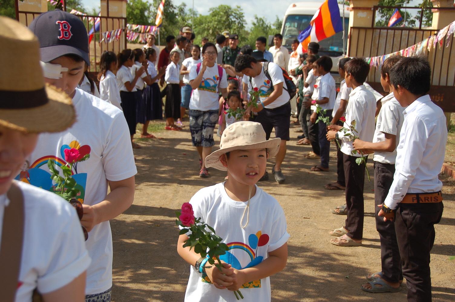 5. 캄보디아 어린이와 마을 주민들이 장미를 나눠주며 한국에서 온 친구들을 환영하고 있다..JPG